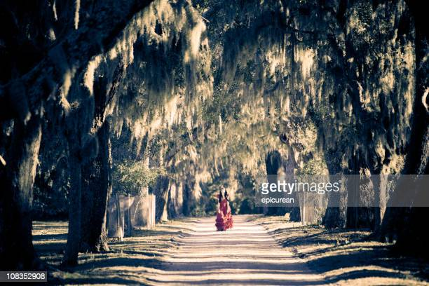 Beautiful woman in red dress walking down white sand road