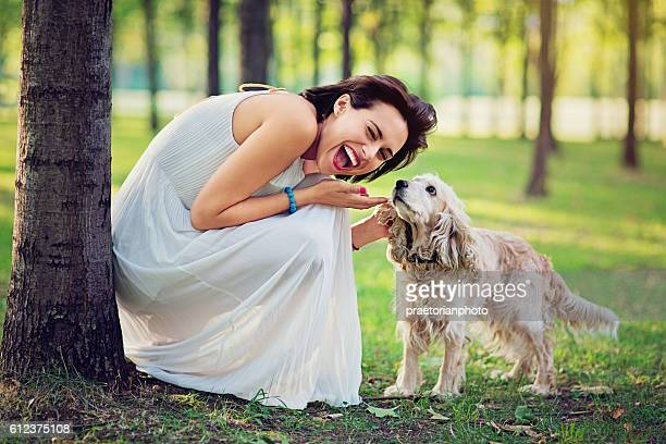 Beautiful woman in the autumn forest playing with her dog