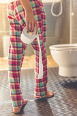 Cropped image of beautiful young woman in pajama holding a toilet paper while going to the toilet