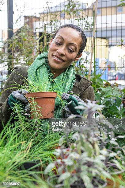 Beautiful Woman In Urban City Garden Potting Plants, London, UK
