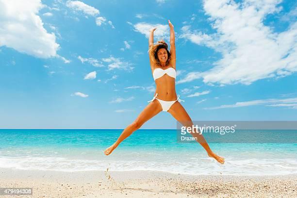 Beautiful woman in white bikini in summer jumping on beach