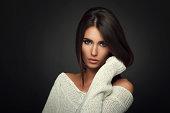 Beautiful woman in white sweater posing in studio on dark background