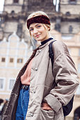 Portrait of a beautiful blonde woman in a cold winter in the historic district. She's wearing a warm winter jacket, pink sweater, jeans, backpack and ears are covered by headband. Captured are also fa