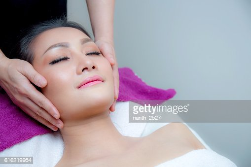 Beautiful woman is getting a facial massage : Stock Photo