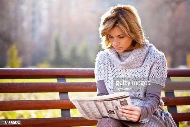 Bella donna leggendo un giornale nel parco.