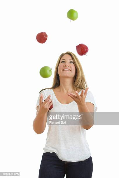A beautiful woman juggling red and green apples.