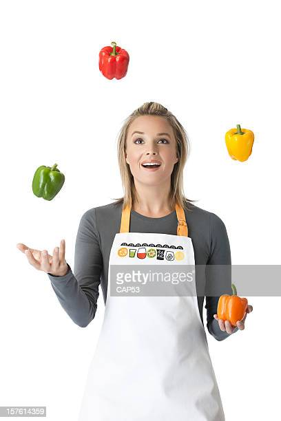 Beautiful woman Juggling With Four Peppers