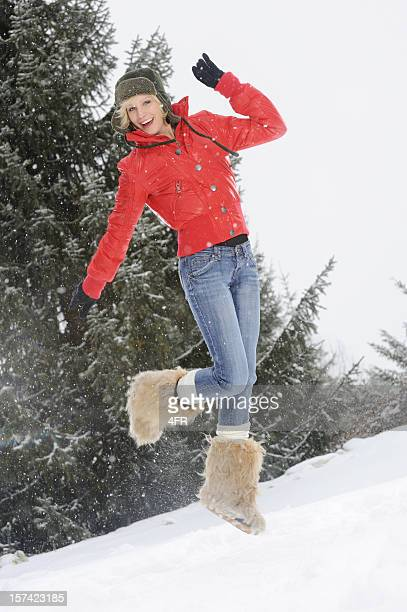 Beautiful Woman jumping through the Snow, Winter Lifestyle