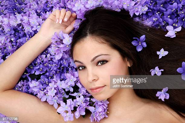 Belle femme soulevant dans un lit de tons violets