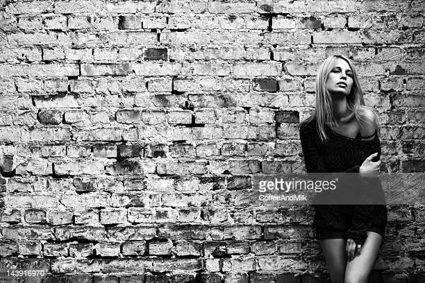 Belle femme s'appuyant sur un mur de briques