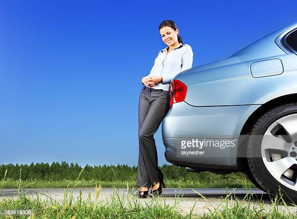 Beautiful woman leans on the car, looking at camera.