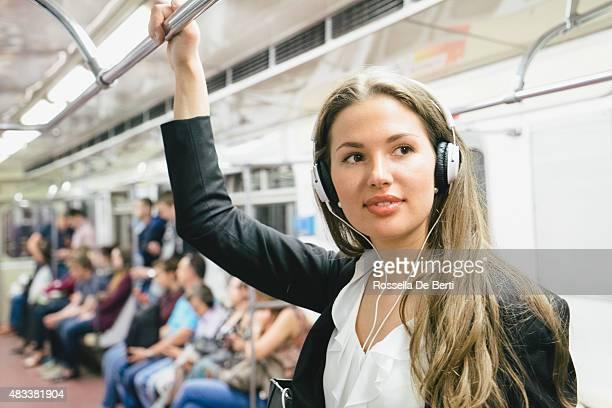 Schöne Frau hören Sie Musik auf Ihrem Smartphone auf U-Bahn