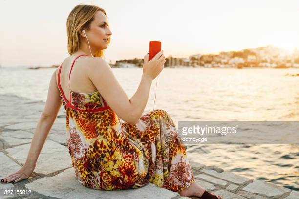 Beautiful woman listening music on vacation in Greece