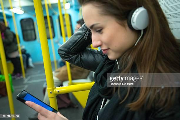 Splendida donna ascoltando musica in Treno della metropolitana