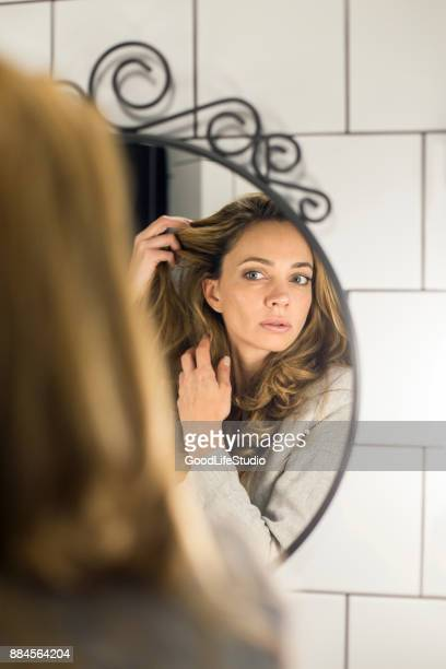 Beautiful woman looking at her hair