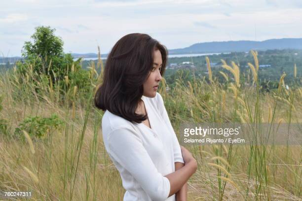 Beautiful Woman Looking Away While Standing On Grassy Field Against Sky