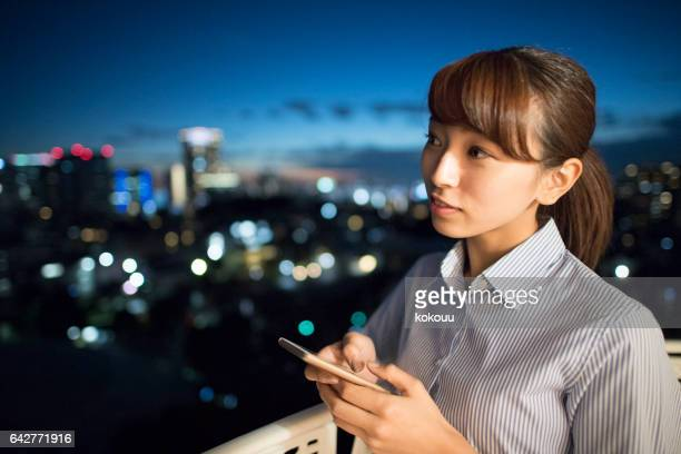 A beautiful woman looks at the night view.