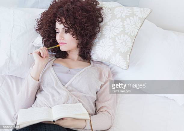 Beautiful woman lying in bed holding diary