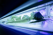 Beautiful woman lying in solarium and sunbathing