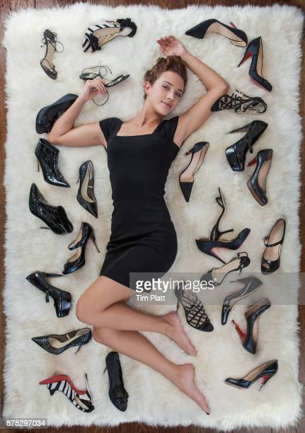 Beautiful woman lying on a rug surrounded by shoes