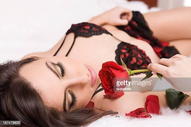 Belle femme allongée sur le lit en Lingerie tenant une Rose
