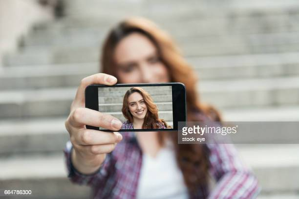 Beautiful woman makes self portrait on smartphone view of screen