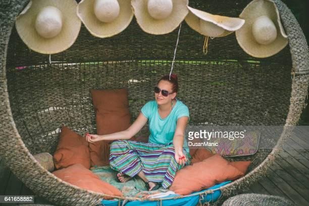 Beautiful woman meditating in a garden chair