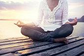 beautiful woman meditating on a boardwalk at sunset