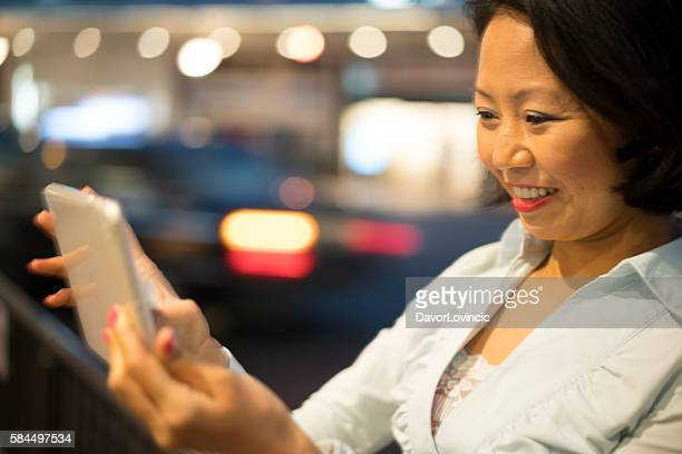 Beautiful woman mobile gaming on street in Kyoto, Japan.