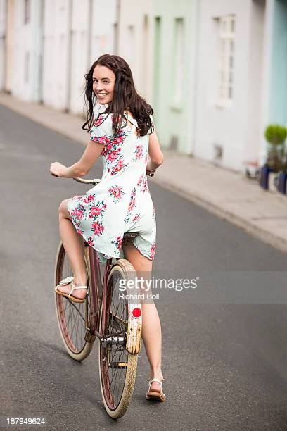 A beautiful woman on a bicycle looking back