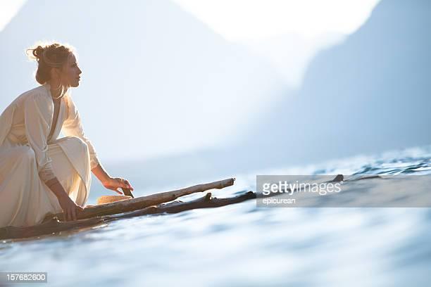 Beautiful woman on a wooden raft