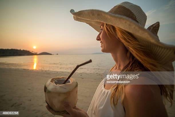 Schöne Frau am Strand schaut bei Sonnenuntergang Holding Kokosnuss