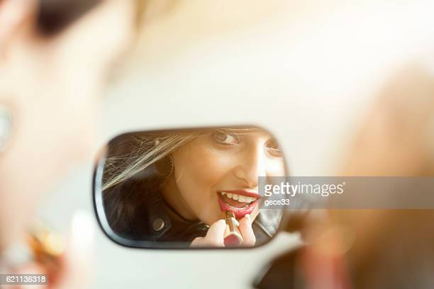 Beautiful woman on motorcycle mirror fixing make up