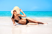 Beautiful woman with perfect body lying down on the beach, wearing stylish hat, tanning on a beach resort, enjoying summer vacation