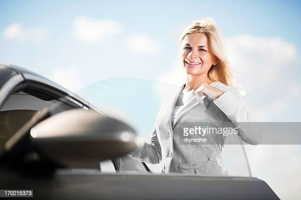 Beautiful woman opening her car door.