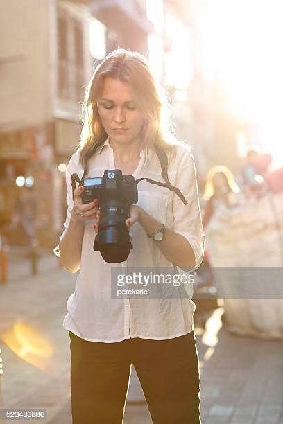 Beautiful woman photographer taking photos in the city