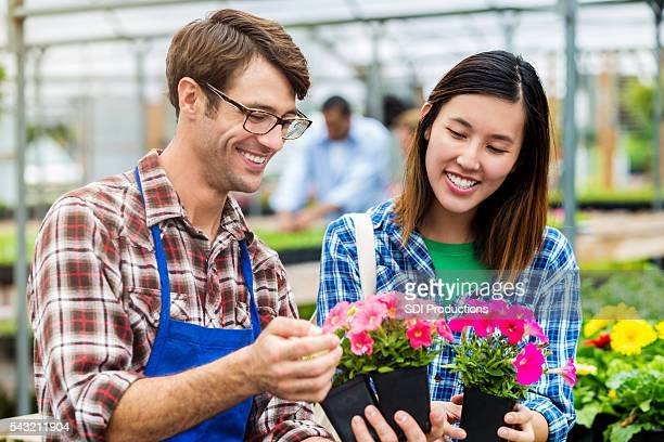 Beautiful woman picking out flowers with handsome nursery employee