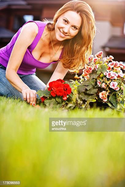 Belle femme planter des fleurs dans le jardin