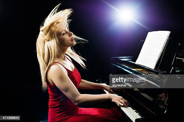 Beautiful woman playing piano with passion.