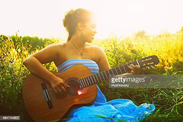 Belle femme jouer de la guitare acoustique dans le champ