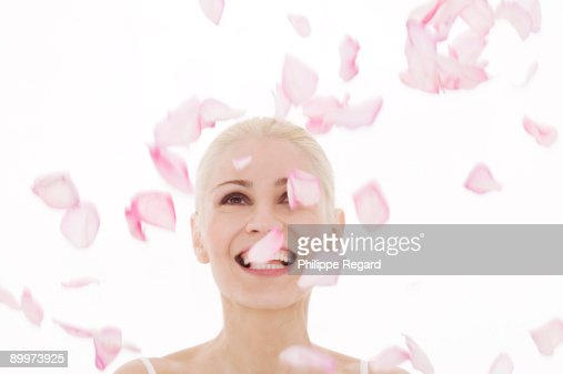 Beautiful woman playing with pink rose petals : Bildbanksbilder