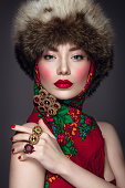 Beautiful woman portrait in russian style with fur hat and scarf