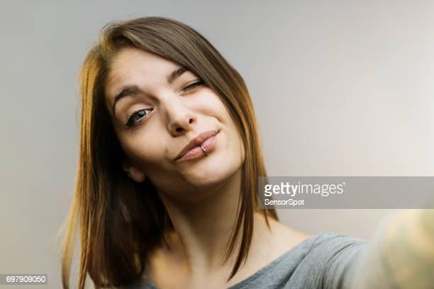 Belle femme posant pour un selfie sur fond gris.