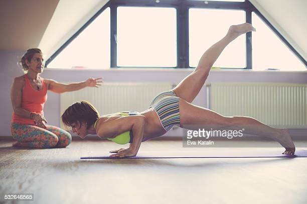 Beautiful woman practicing bikram yoga with her trainer
