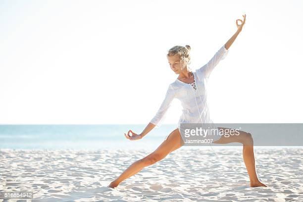 Belle femme pratiquer le Yoga sur la plage