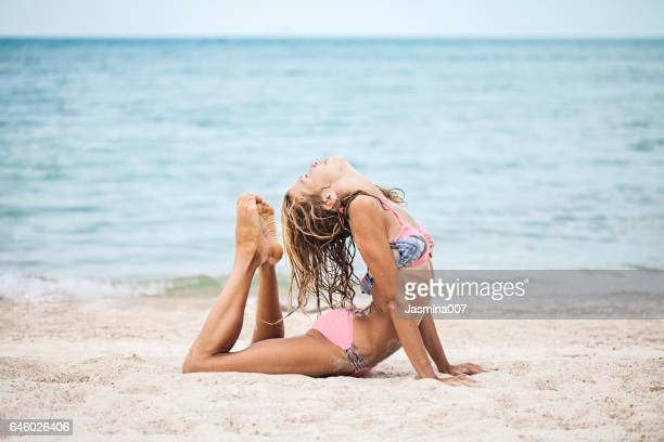 Beautiful woman practising yoga on the shoreline