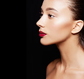 Perfect skin bronze skin caucasian woman isolated on black. Red lipstick. Make-up image.