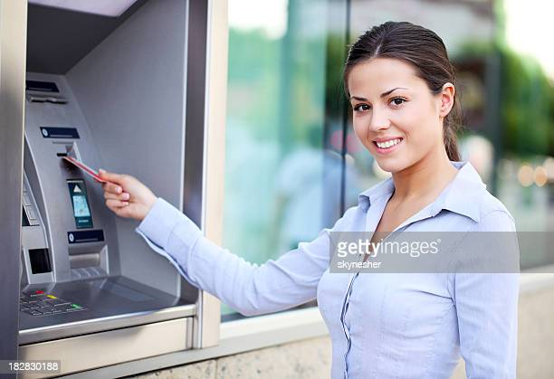 Beautiful woman put her credit card at the ATM.