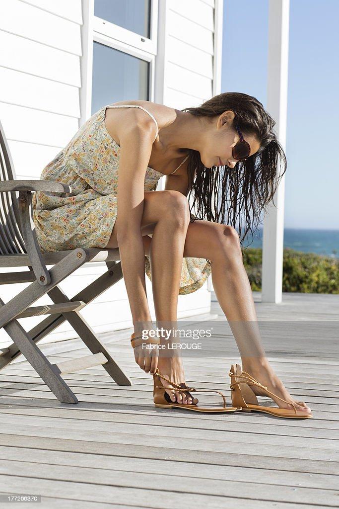 Beautiful woman putting on sandal at beach resort
