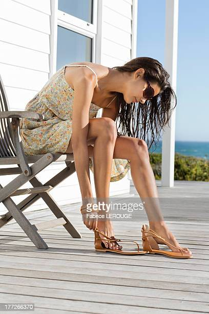 Beautiful woman putting on sandal at beach resort